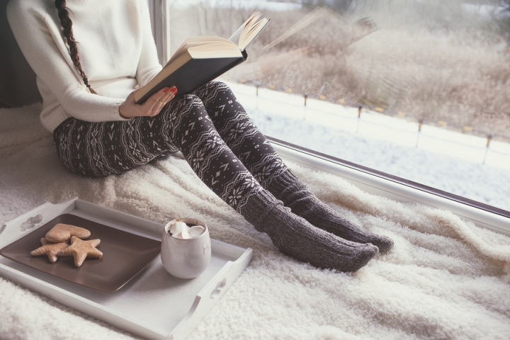 Young woman with cup of coffee and gingerbread is reading a book