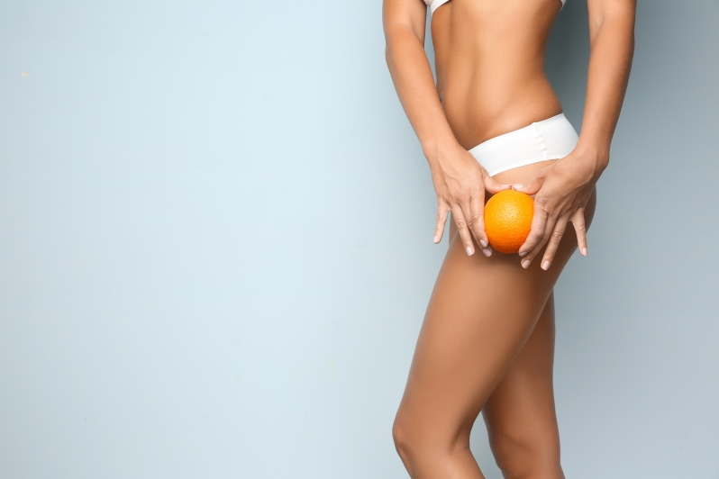 Young woman holding orange on light background. Cellulite proble