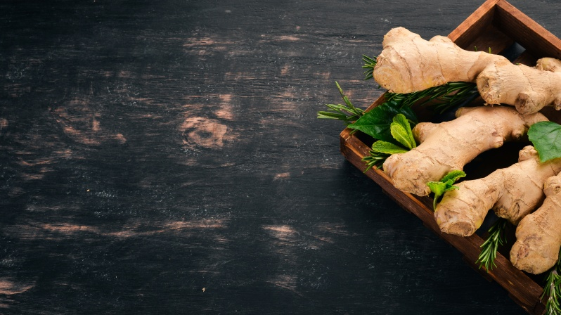 Fresh ginger on a wooden background. Top view. Copy space.